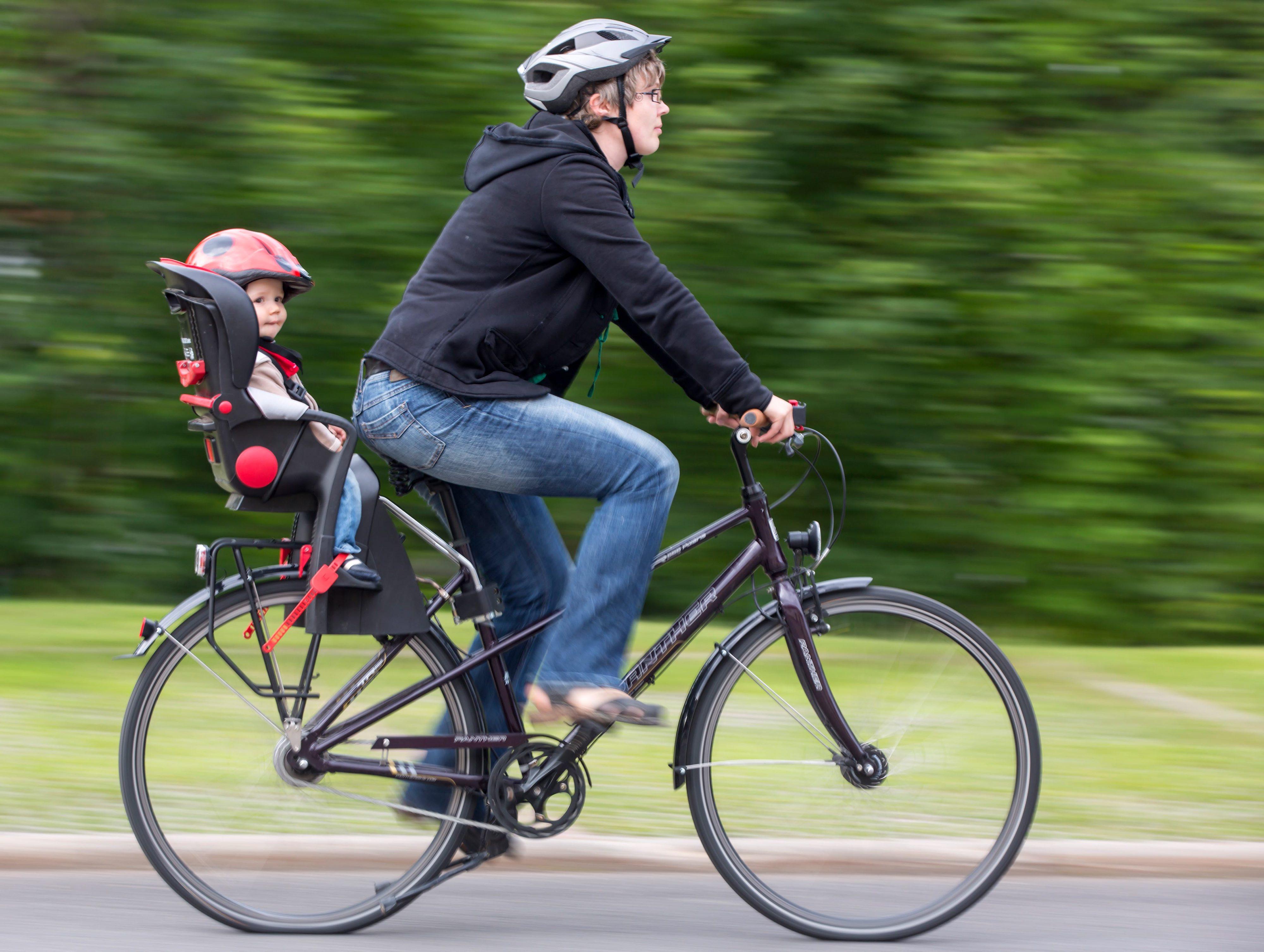 MODEL RELEASED - Eine Mutter fährt am 27.06.2012 inIlmenau mit dem Rad, ihr neun Monate altes Kind Anton sitzt auf dem Fahrradsitz. Foto: Michael Reichel